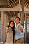 Stock photo of an hispanic couple toasting their new home.  Exposed beams, studs, and two by fours in the background.